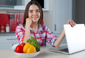 Young woman sitting at kitchen table with laptop and vegetables bowl