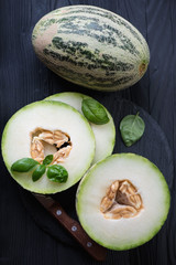 Top view of sliced and whole melons on a black wooden surface