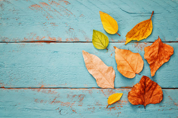 Autumn background with dry leaves on wooden table