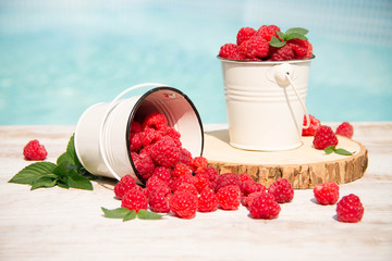 Sweet raspberries in bowl on wooden table. Close up, top view