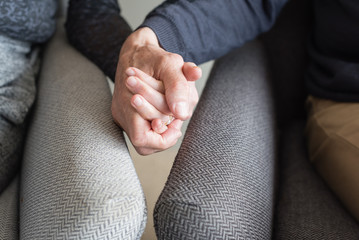 Close up of older couple in armchairs holding hands (cropped and selective focus)
