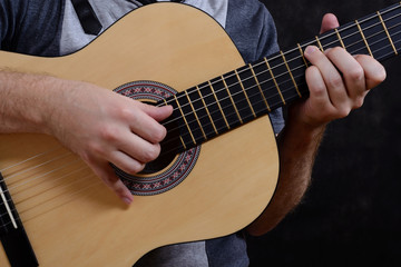 Acoustic guitar guitarist playing details. Musical instrument with performer hands