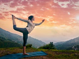 Woman doing yoga asana Natarajasana outdoors at waterfall