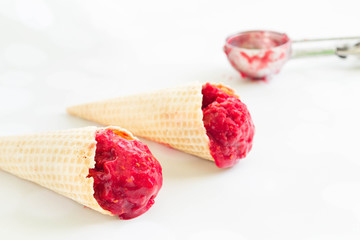 Homemade red berry ice cream in cones, white background