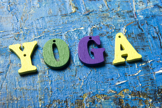 Yoga word made of wooden colorful letters on vintage background