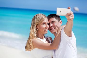 Romantic couple taking selfie on Caribbean beach