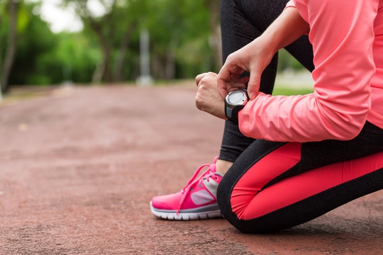 Sports athlete runner woman looking at heart rate monitor after