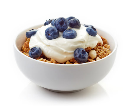 Bowl of whole grain muesli with yogurt and blueberries isolated