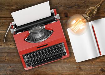 Retro-Schreibmaschine und Glühbirne mit Notizbuch - Textfreiraum