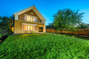 Wooden house with meadow in front of it