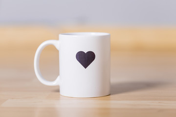 White mug with dark heart painted on it