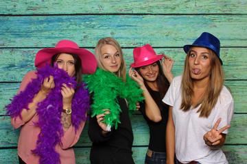 Junge Mädchen mit Hüte und Federboas strecken die Zungen heraus - Photobooth Party