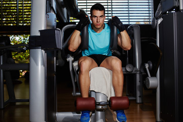 Young athletic man exercise with abs muscles on press machine