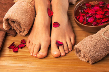 Beautiful female feet, spa salon, pedicure procedure with petals of red rose flower