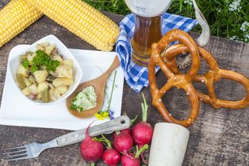 Imbiss mit Brezeln, Bier und Kartoffel-Bohnensalat, Makro von oben