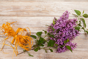 purple lilac branch, gift box on wooden background. Blank