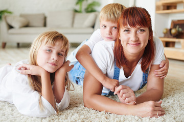 Portrait of mother with her daughter and son lying on the carpet on the floor of the house