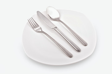 Cutlery . Fork, knife, spoon on a white plate. White background. Studio