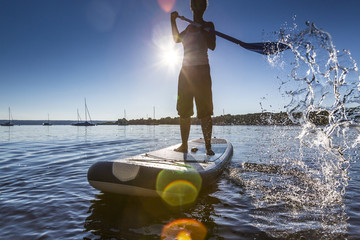 Woman paddleboarding in the lake Ammersee, Bavaria, Germany