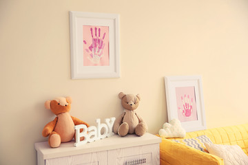 Frames with family hand prints in room interior