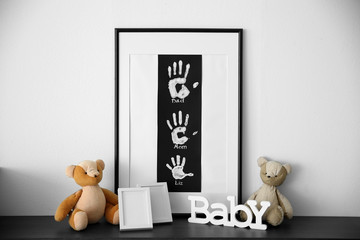 Frame with family hand prints and home decor in room