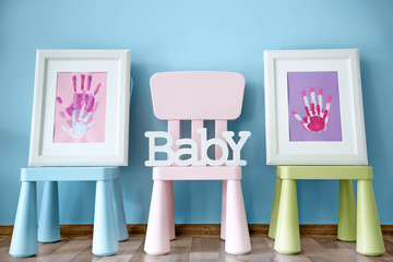Frames with family hand prints on chairs in room