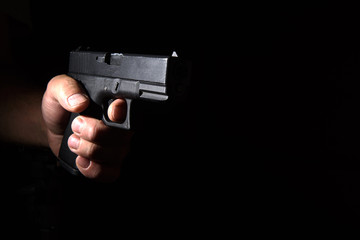 Glock pistol in his hand in the dark closeup
