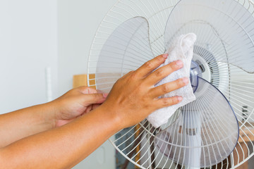 Close up horizontal photo of male hand cleaning dirty electric fan