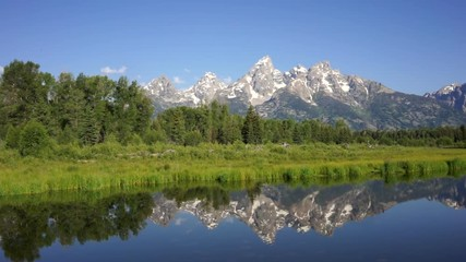 Wall Mural - The water is perfectly smooth showing high peak reflections in the Teton's