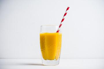 Glass of fresh orange juice on the white wooden background