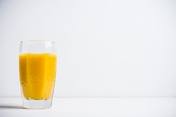 Glass of fresh orange juice on the white wooden background
