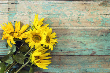 Background with a bouquet of sunflowers on old wooden boards wit