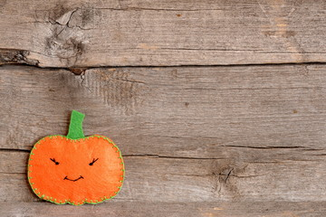 Halloween cute orange pumpkin on an old wooden background with blank place for text. Halloween kids craft background. Home felt pumpkin decor
