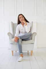 Charming girl is smiling while sitting in an armchair