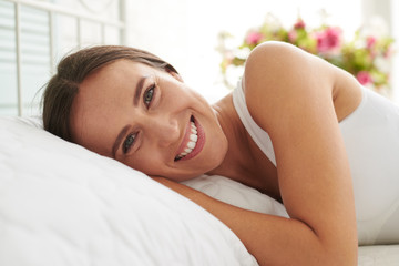 Happy smiled woman lying on the bed in the morning