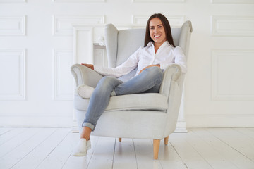 Young pretty woman relaxing and having rest on armchair