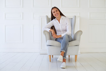 Young woman sitting in a modern armchair relaxing in her room