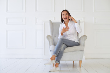 Young woman with surprised expression while talking on the phone