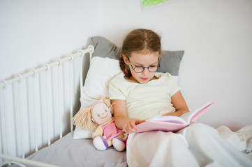 Little girl in glasses reading a book while lying in be