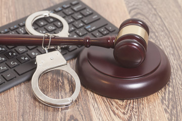 Computer keyboard,handcuffs and judge gavel on wooden background