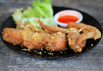 Fried chicken in black dish with sauce and vegetable.