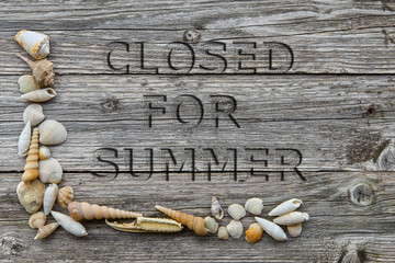 """written engraved on wooden table """"closed for the summer"""" with the shells"""