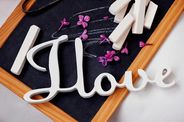 Wooden slate with chalk and vintage scissors . Lilac purple, The inscription I love.