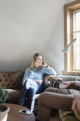 Young woman holding coffee cup while looking at friend in cafe