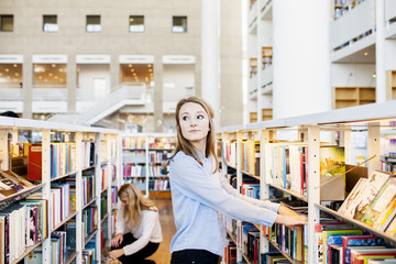 Young university student looking away while choosing book in library