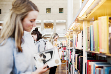 Female university students choosing books in library