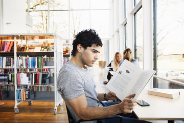 Young man reading book at table in library