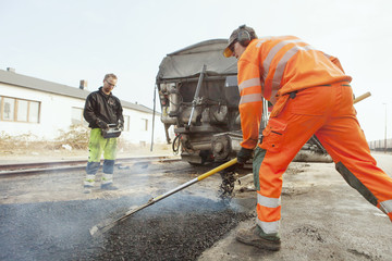 Manual workers paving at road construction site
