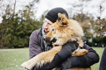 Man embracing Eurasier at park
