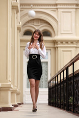 Beautiful brunette woman wearing white blouse and black skirt